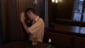 Drunk guy sitting at a table in a pub and drinking beer -. Drunk guy sitting at a table in a pub and drinking beer stock video