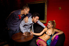 Two guys  flirting with stripteaser Royalty Free Stock Photo