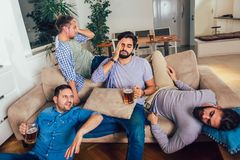 Drunk guys are sleeping after night events on the floor and sofa in different pose in living room stock photos