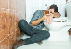 Drunk hispanic man sleeping over the toilet bowl Royalty Free Stock Photography