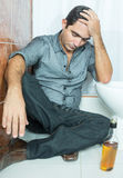 Drunk latin man sleeping on the toilet Royalty Free Stock Image