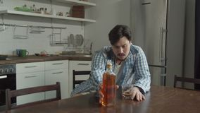 Man drinking alcohol sitting at kitchen table. Drunk male pouring alcoholic drink from bottle into glass, depressive man alone relieving stress and family stock video