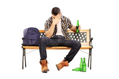 Drunk male teenager sitting on a bench and drinking beer Royalty Free Stock Photos