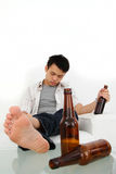 Drunk man. A drunk man sitting on a couch with some beer bottles Royalty Free Stock Photo
