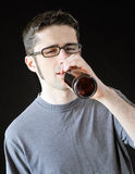 Drunk man. Intoxicated young man drinking out of a brown beer bottle Stock Image
