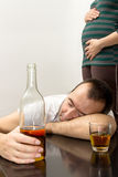 Drunk man. Lying on the table in the background pregnant woman Royalty Free Stock Photography
