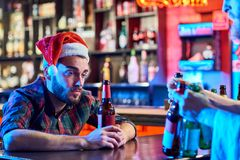 Drunk Man Alone on Christmas. Portrait of sad young men wearing Santa hat getting drunk alone sitting at bar counter drinking beer at Christmas, copy space Stock Photography