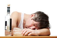 Drunk man asleep at table with glass of vodka Royalty Free Stock Images