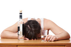 Drunk man asleep at table with glass of vodka Stock Image
