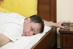 Drunk man in bed Royalty Free Stock Images