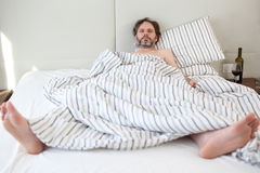 Drunk man in bed. Drunk mature man sleeping in his bed Royalty Free Stock Photography
