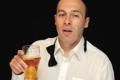Drunk man with beverage. Man with eyes half shut, tie undone, holding a beer, caucasian/white Royalty Free Stock Image