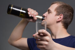 Young drunk man with bottle of alcohol and glass Stock Images