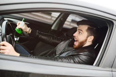 Drunk man with a bottle of beer driving a car. Drunk young man with a beard with a bottle of beer in his hand behind the wheel of a car. Emergency situation Stock Photos