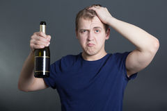 Drunk man with bottle of champagne over grey Royalty Free Stock Photos