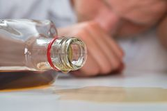 Drunk Man With A Bottle Of Liquor. Young Drunk Man Sleeping On Table With A Bottle Of Liquor Royalty Free Stock Images