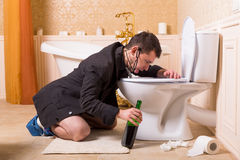 Drunk man with bottle of wine sick in toilet bowl. Funny drunk man with bottle of wine sick in the toilet bowl. Luxury bathroom interior on background royalty free stock photography