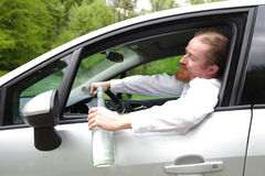 Drunk man in car. With a bottle alcohol Royalty Free Stock Photo
