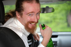 Drunk man in car. With a bottle alcohol Stock Photo