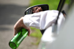 Drunk man in car. With a bottle alcohol Royalty Free Stock Photography