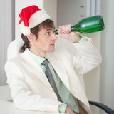 Drunk man in Christmas cap with bottle Royalty Free Stock Image