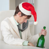 Drunk man in a Christmas cap with bottle Royalty Free Stock Images