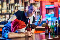 Drunk Man at Christmas Party in Bar. Portrait of drunk men wearing Santa hat laying on bar counter drinking beer and throwing money around after Christmas party Royalty Free Stock Photo