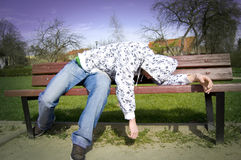 Drunk man conceptual image. A drunken man lying on a park bench Royalty Free Stock Photo