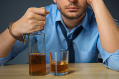 Drunk man drinking alcohol at the table Stock Images