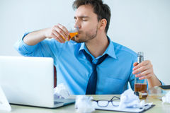Drunk man drinking alcohol while working. Can not stop. Drunk gloomy man holding glass with alcohol and drinking it while sitting at the table at work Stock Photography