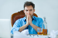 Drunk man drinking alcohol while working. I need help. Tired hopeless gloomy man sitting at the table and looking at the bottle of alcohol Stock Photo