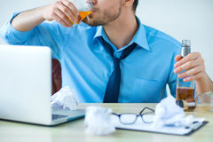 Drunk man drinking alcohol while working Stock Photo