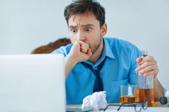 Drunk man drinking alcohol while working Stock Photos