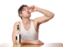 Drunk man drinks a glass of vodka Royalty Free Stock Image