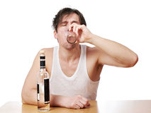 Drunk man drinks a glass of vodka Stock Images