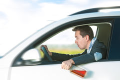 Drunk man driving car with bottle in hand. Drunk man holding bottle of whiskey in left hand. Person driving and drinking alcohol. Outdoor action with young guy Stock Photo