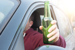 Drunk man driving his car and drinking Royalty Free Stock Images