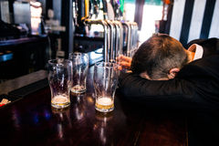 Drunk man with empty glasses. In a bar Stock Images