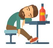 Drunk man fall asleep in the pub. A drunk man sitting fall asleep on the table with a bottle of beer inside the pub. Over drink concept. A Contemporary style Stock Photos