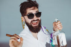 Drunk man having fun at wild party. Bearded man with sunglasses holding a bottle of alcohol and cigar at celebration. Ecstatic portrait of drunk man having fun Stock Images