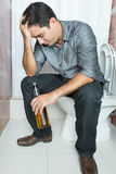 Drunk man with a headache sitting on the toilet Stock Image