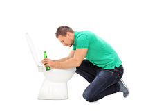 Drunk man leaning on a toilet Royalty Free Stock Photography