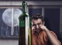 Drunk man looks at the bottle Royalty Free Stock Image