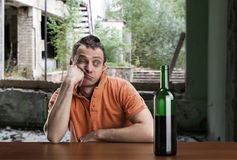 Drunk man looks at the bottle Royalty Free Stock Photos