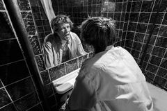 Drunk Man looks at himself in the mirror Stock Photography