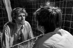 Drunk Man looks at himself in the mirror Royalty Free Stock Photos