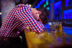 Drunk man lying on bar counter Royalty Free Stock Images