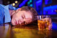 Drunk man lying on bar counter. Drunk young man with whiskey glass lying on bar counter Stock Photo