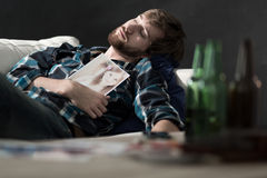 Drunk man lying on couch stock photo