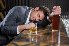 Drunk man lying on a counter with bottle of whisky Stock Photography